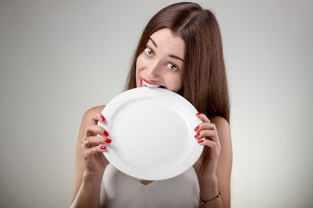 Egy nő egy üres tányért rág